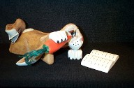 Rabbit laying down eating a carrot or red chili reading a book, woodcarving art